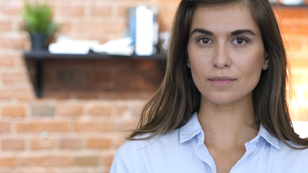 Latin Girl Looking in Camera, Standing in Her Loft Office Stock Photo