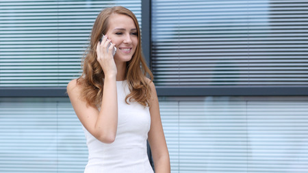 Busy Talking on Smartphone, Standing Outside Office