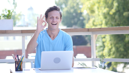 Ok, Sign of Okay by Young Man at Work, Sitting on Desk, Outdoor Stock Photo