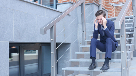 Tired Frustrated Young Businessman Sitting on Stairs Outside Office Stock Photo