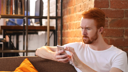 Relax Man Using Smartphone, Sitting on Sofa Stock Photo