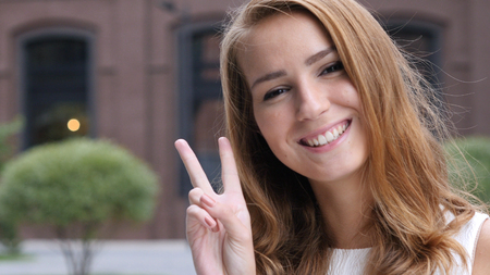 Sign of Victory by Beautiful Girl Face, Outdoor Portrait Stock Photo