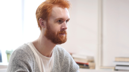 Serious Man with Red Hairs in His Creative Office