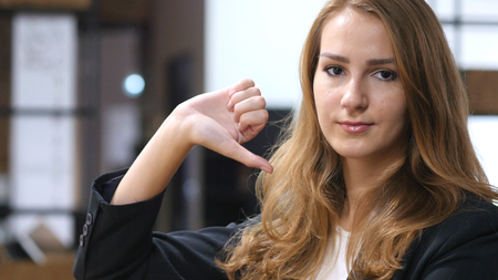 Thumbs Down by Beautiful Girl Sitting Indoor, Portrait Stock Photo