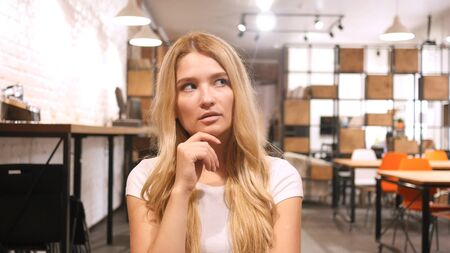 Young Girl Thinking in Office Stock Photo