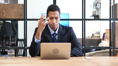Black Businessman Upset by Loss while Working Online