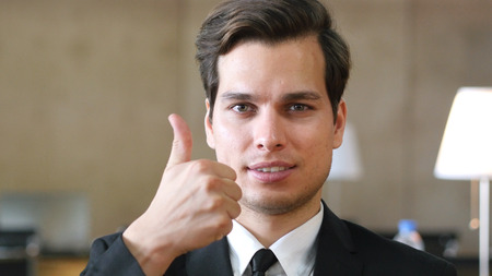 Thumbs Up by Businessman, Portrait in Office Stock Photo