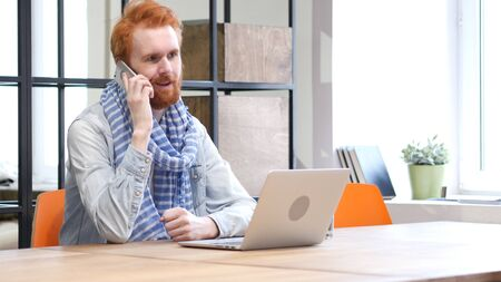 Phone Negotiation by Man while Working on Laptop