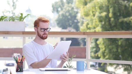 Paperwork, Designer Editing Designs Sitting in Balcony of Office Outdoor