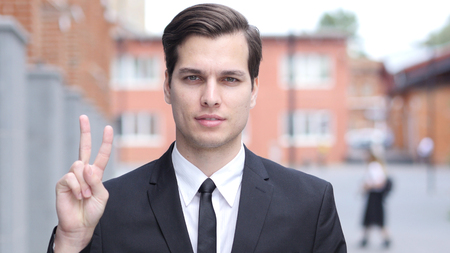 Sign of Victory by Successful Businessman in Suit, Outside Office