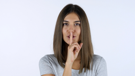 Gesture of silence, Finger on Lips by Beautiful Girl, White Background in Studio Stock Photo