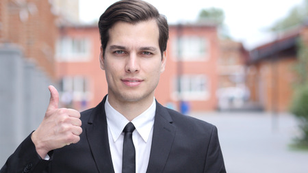Thumbs Up by Successful Businessman in Suit, Outside Office Stock Photo