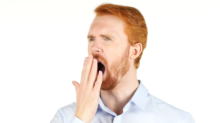Tired businessman yawning against a white background Stock Photo