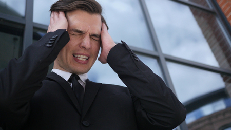Frustrated, Tense Young Businessman with Headache and Problems Stock Photo