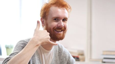 Call Us, Contact Us, Gesture by Man with Red Hairs Stock Photo