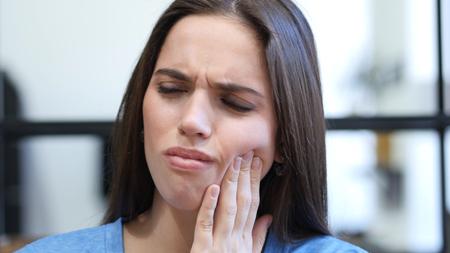 Mal di denti, donna che soffre di dolore nei denti, al coperto