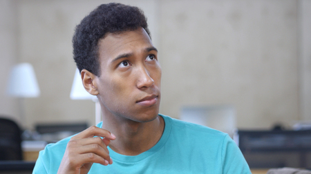 Thinking Pensive Black Young Man in Office, Portrait Stock Photo