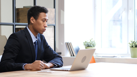 Online Video Chat on Laptop by Black Businessman Stock Photo