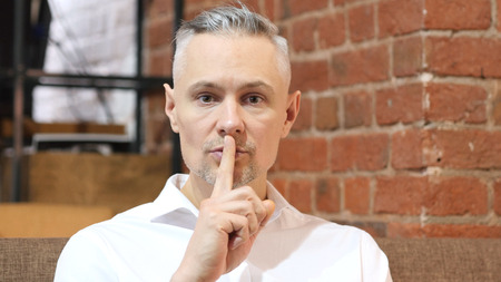 Gesture of Silence by Middle Age Man, Finger on Lips Standard-Bild