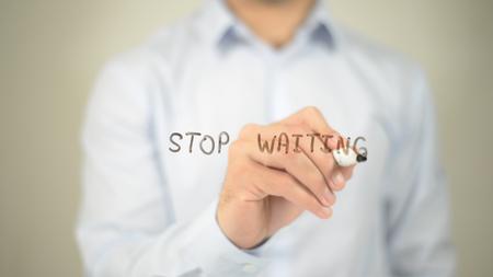Stop Waiting , man writing on transparent screen