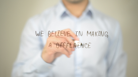 We Believe In Making A Difference , man writing on transparent screen Stock Photo