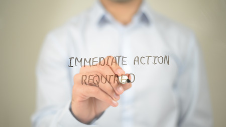 Immediate Action Required , Man writing on transparent screen Stock Photo