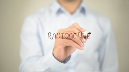 uranium: Radioactive, Man Writing on Transparent Screen Stock Photo