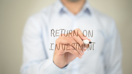 Return on Investment,  Man writing on transparent screen