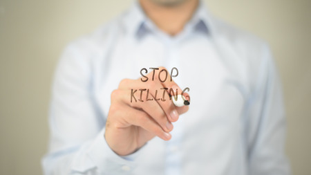 against the current: Stop Killing , man writing on transparent screen