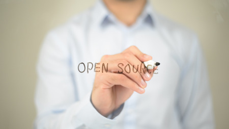 Open Source , Man writing on transparent screen Stock Photo