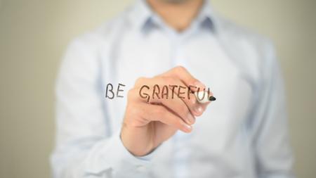 Be Grateful, man writing on transparent screen