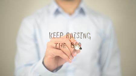 Keep Rising the Bar , Man writing on transparent screen Imagens