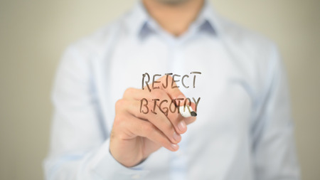 Reject Bigotry , man writing on transparent screen