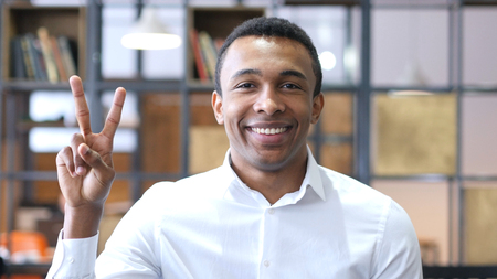african business: Victory Sign by Black Man in Office