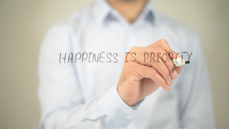 Happiness Is Priority , man writing on transparent screen