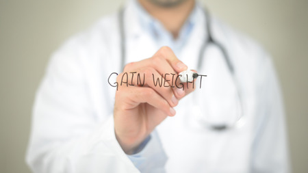 sliding scale: Gain Weight, Doctor writing on transparent screen Stock Photo