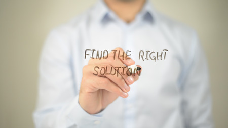 Find The Right Solution , man writing on transparent screen Stock Photo