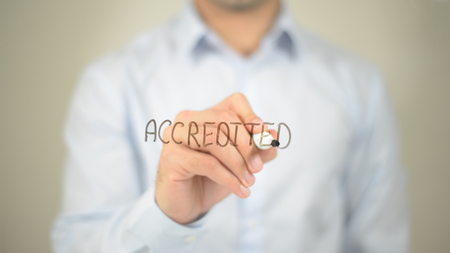Accredited, man writing on transparent screen