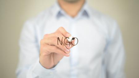 NGO,  Man writing on transparent screen 免版税图像