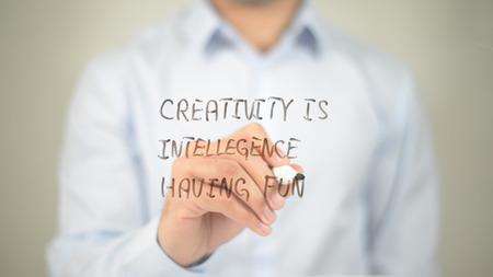 Creativity Is Intelligence Having Fun , man writing on transparent screen