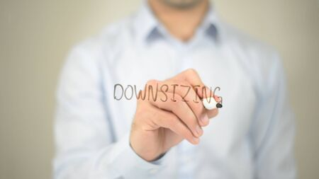 Downsizing , man writing on transparent screen Stock Photo