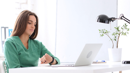 Woman Watching Time on Watch while Waiting in Office