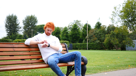 fantasize: Using Smartwatch, Man Sitting in Park on Bench, Red Hairs and Beard