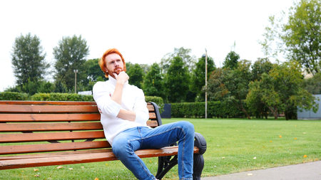 fantasize: Thinking Man Sitting in Park on Bench, Red Hairs and Beard Stock Photo
