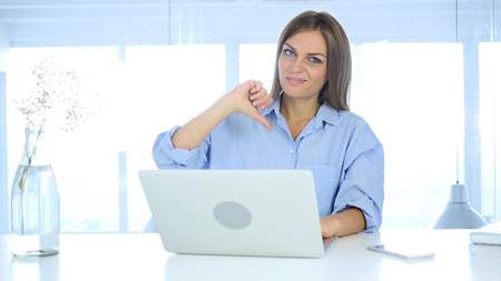 Thumbs Down, Frustrated Woman Gesture while Sitting in Office Stock Photo