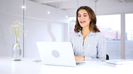 Happy Woman Doing Video Chat on Laptop in Office for Work