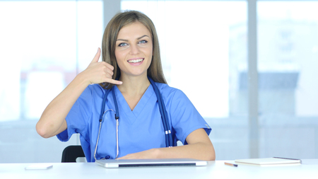 Young Female Doctor Call Us for Help Gesture Stock Photo