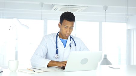 Afro-American Doctor Typing on Laptop in Hospital Stok Fotoğraf