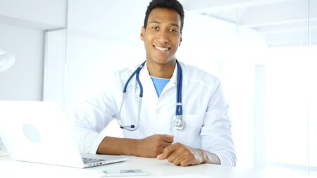 Afro-American Smiling Positive Doctor in Clinic Looking at Camera Standard-Bild - 88961324