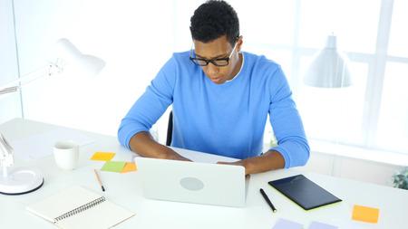 オフィス、クリエイティブフリーランサーデザイナーでノートパソコンに取り組んで